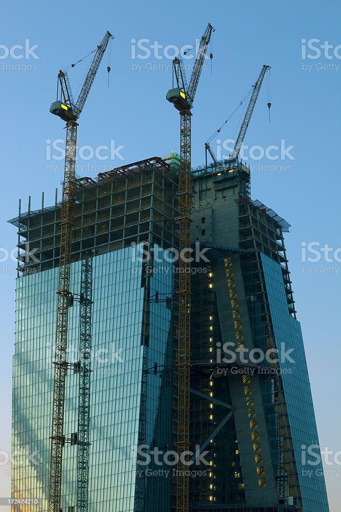 Skyscraper Under Construction with Cranes at Dusk, Frankfurt, Germany royalty-free stock photo