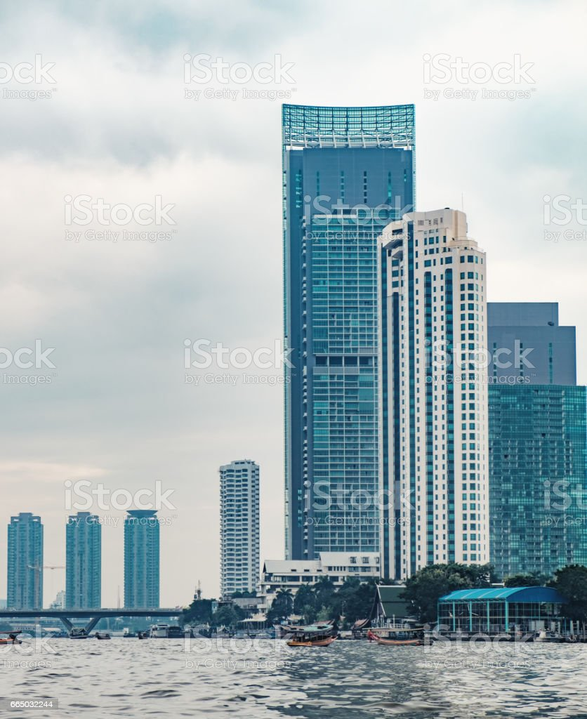 Skyscrapers, bridge and boats on river in Bangkok stock photo