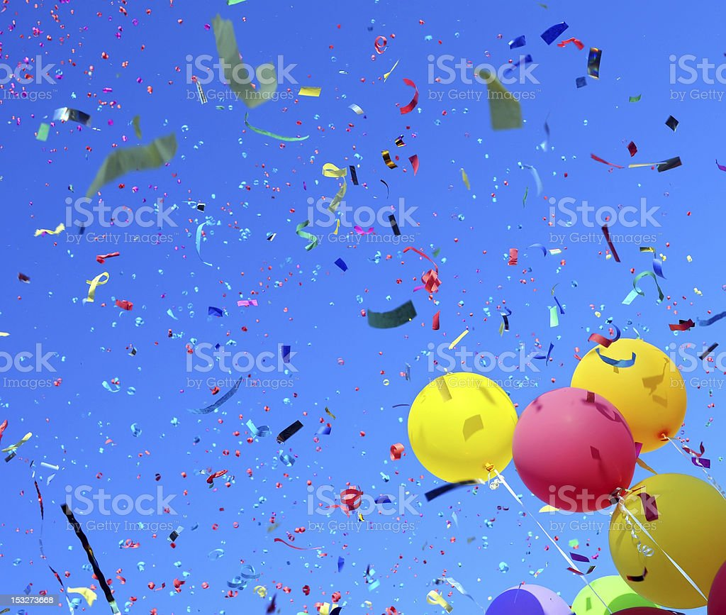 Skyward view of colorful balloons and falling confetti stock photo