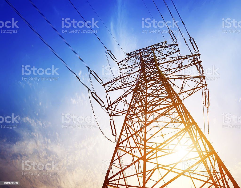 Skyward view of high voltage tower under blue sky stock photo