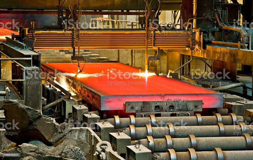 Slab of hot steel being processed on conveyor belt stock photo