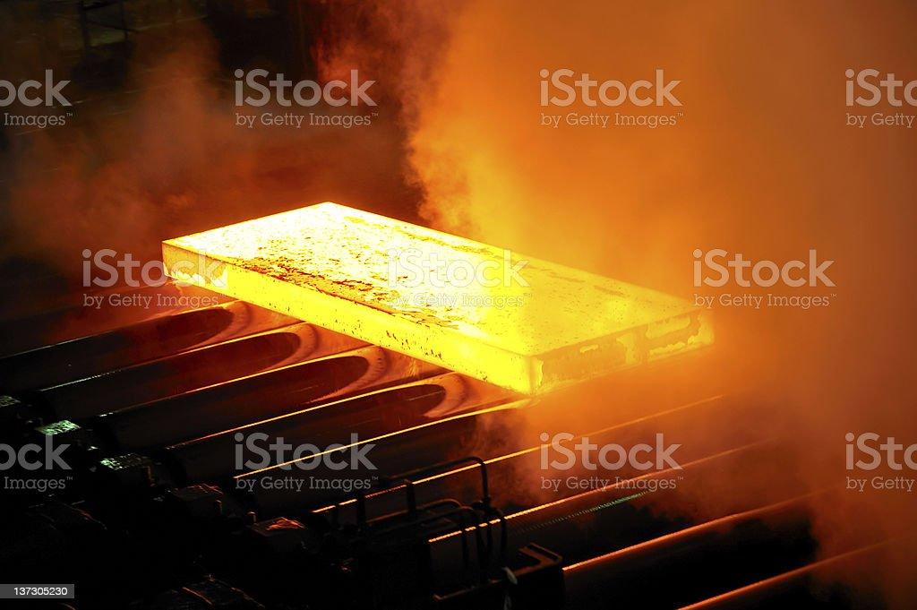Slab of steel burning yellow sliding along conveyor belt stock photo