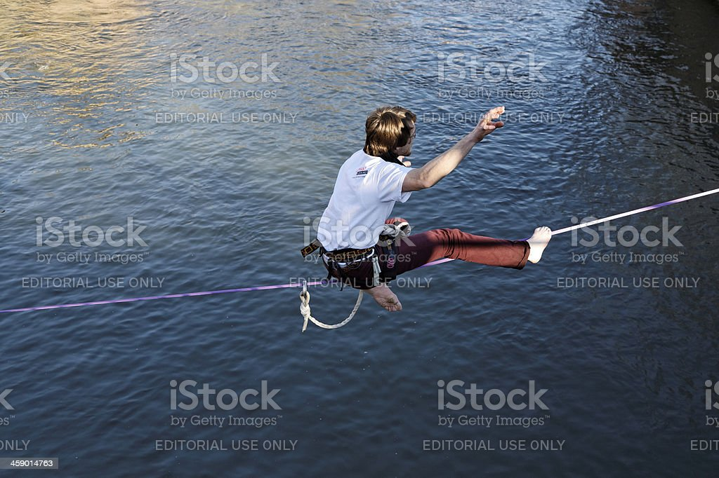 slackline - man sitting on rope stock photo