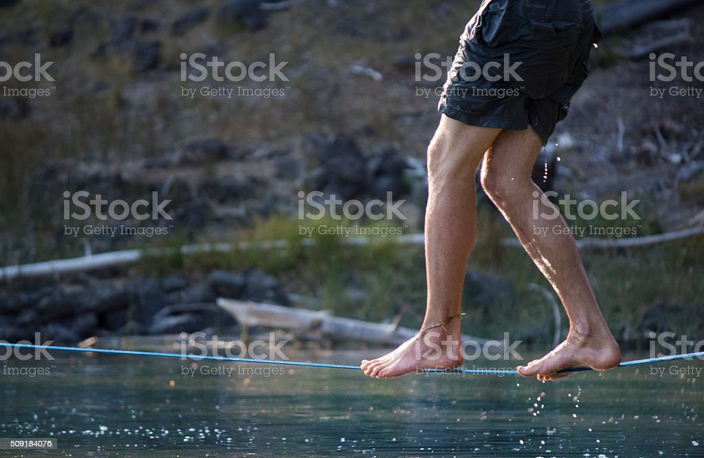 Slackline over water, tight rope walker stock photo