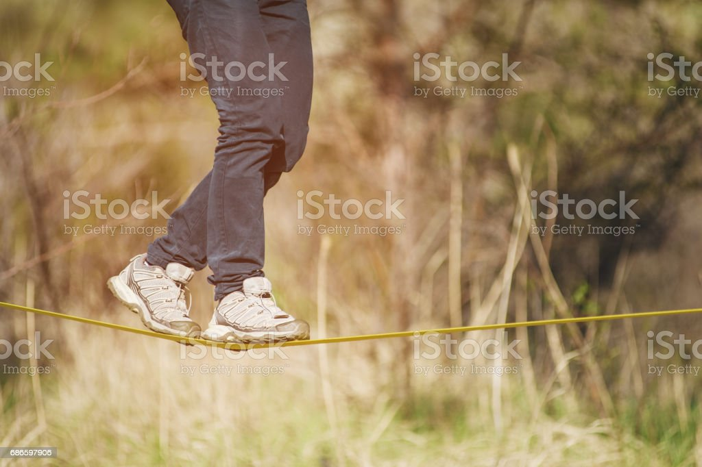 Slacklining is a practice of balancing, in which nylon or polyester fabric stretched between two anchor points is commonly used. People walk on it and do tricks stock photo