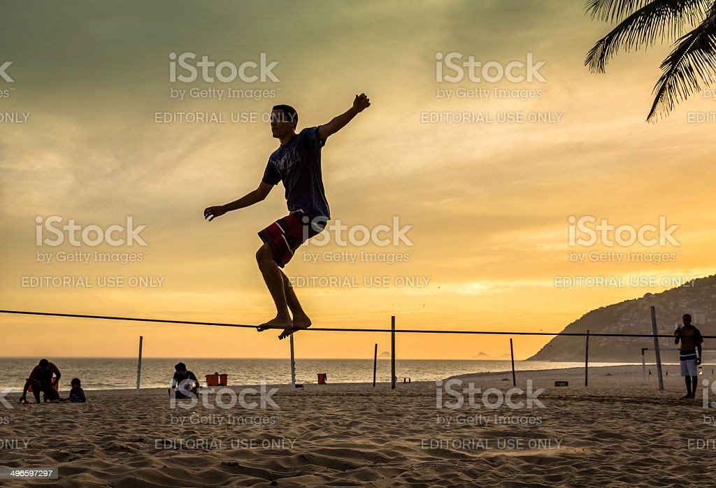 Slacklining on the beach in Rio de Janeiro during sunset stock photo