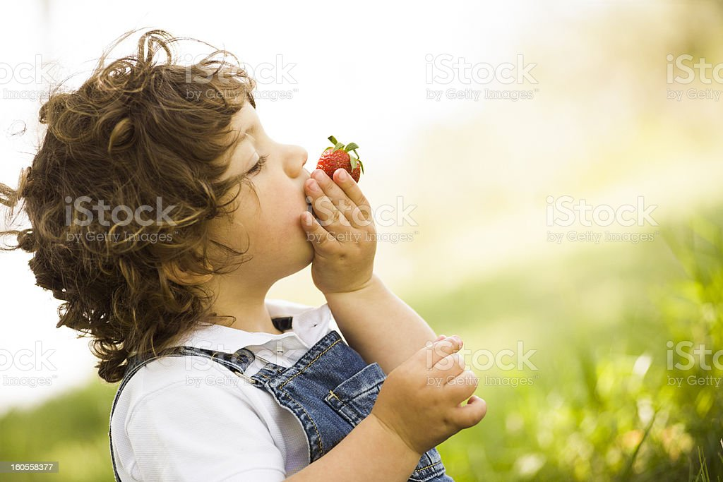 Slanted close-up shot of a young boy tasting a strawberry stock photo