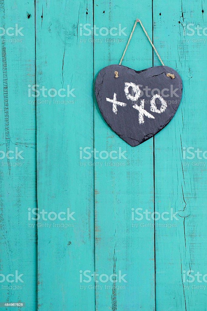 Slate heart with XOXO hanging on door stock photo