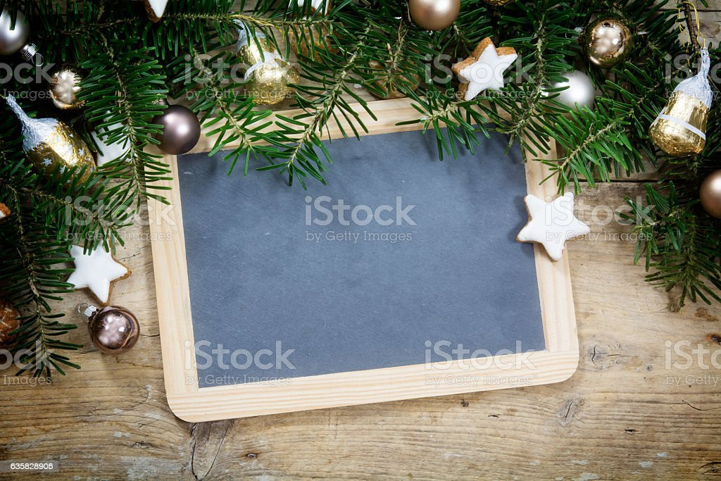 Slate writing board with fir tree branches and Christmas decoration stock photo