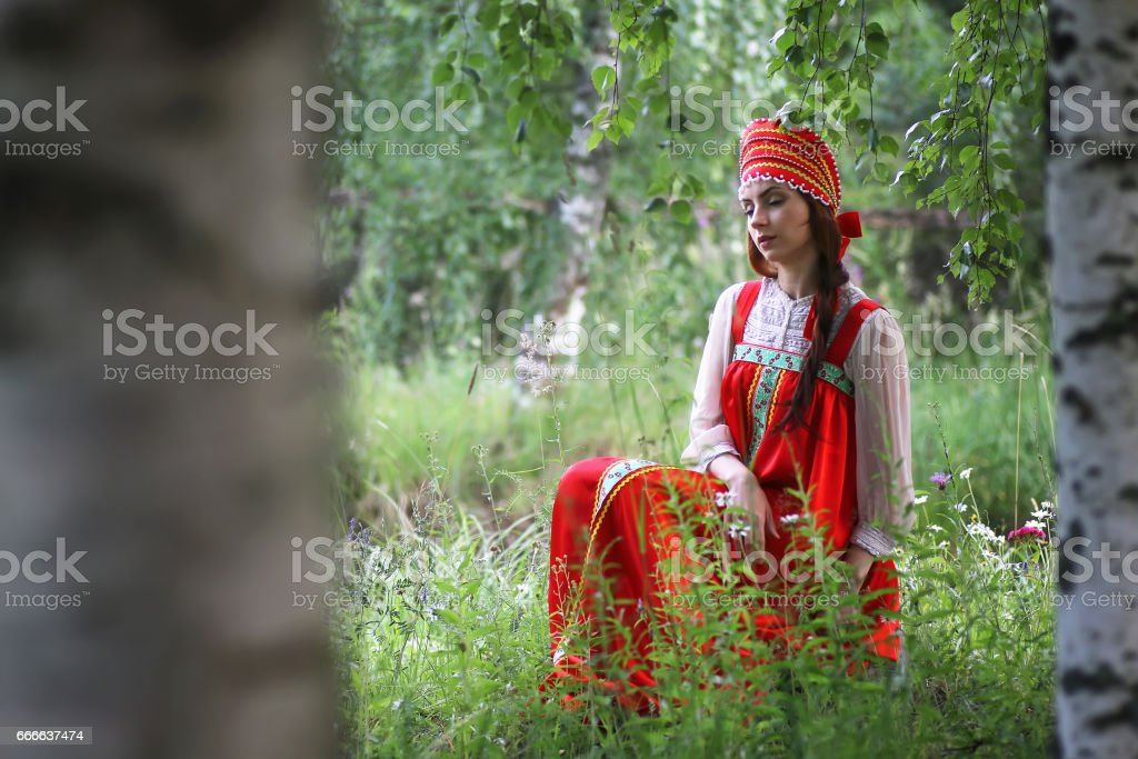 Slav in traditional dress is sitting in nature stock photo