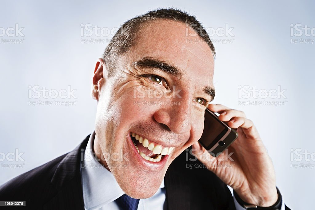 Sleazy man tries too hard, giving cheesy grin on phone stock photo