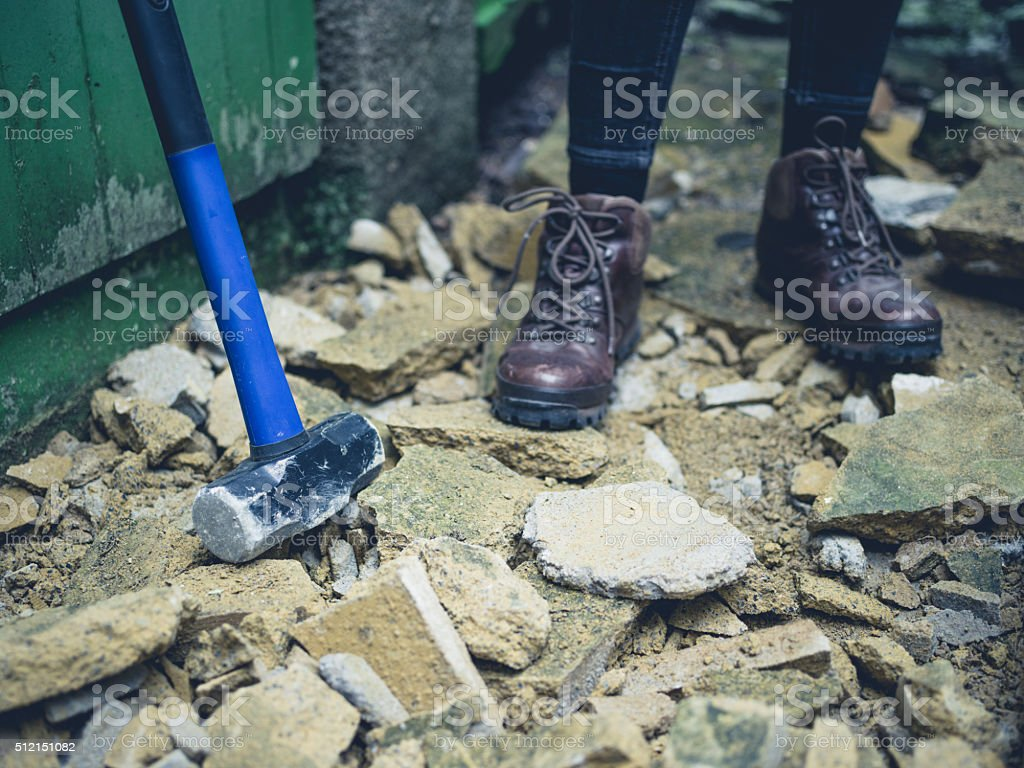 Sledge hammer outside by person's feet stock photo