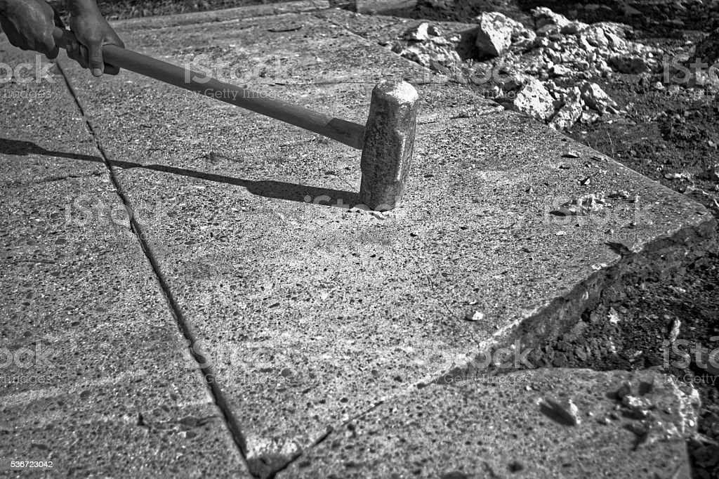 Sledgehammer impacts concrete slab stock photo