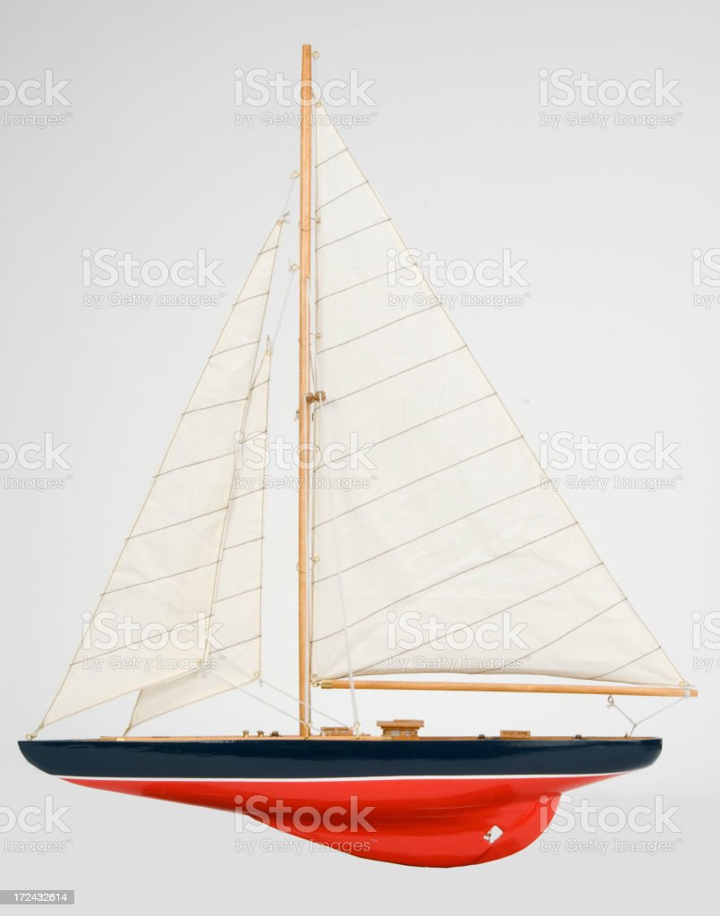 Sleek black and red single masted sailboat-isolated on white royalty-free stock photo