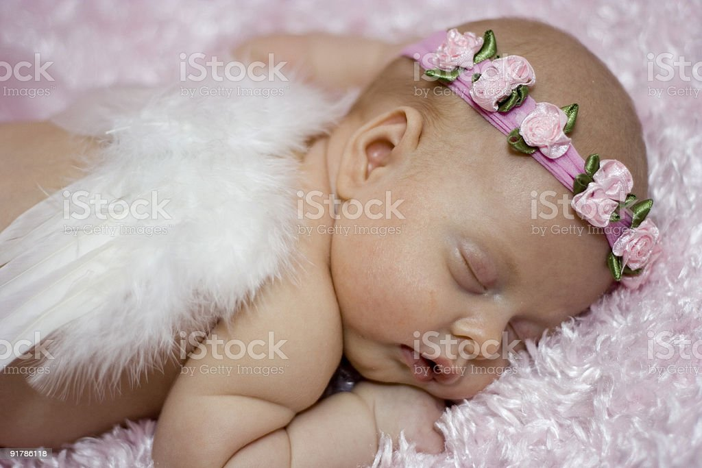 A sleeping angel with a flower headband and wings stock photo