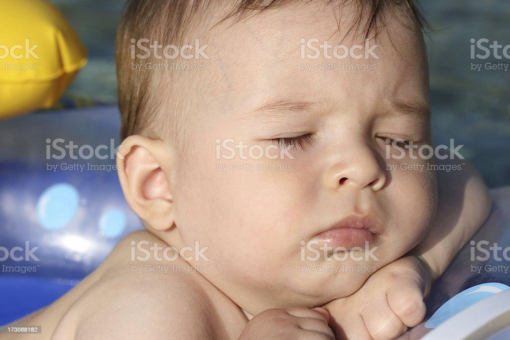 sleeping baby boy face on the sea stock photo