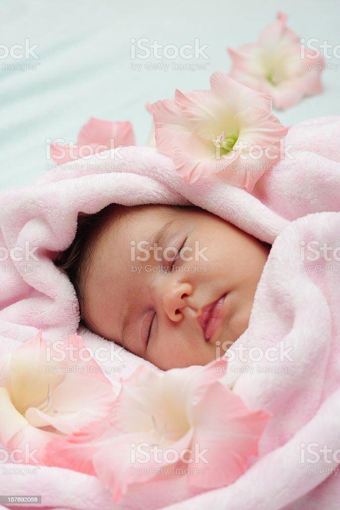 Sleeping baby girl with flowers stock photo