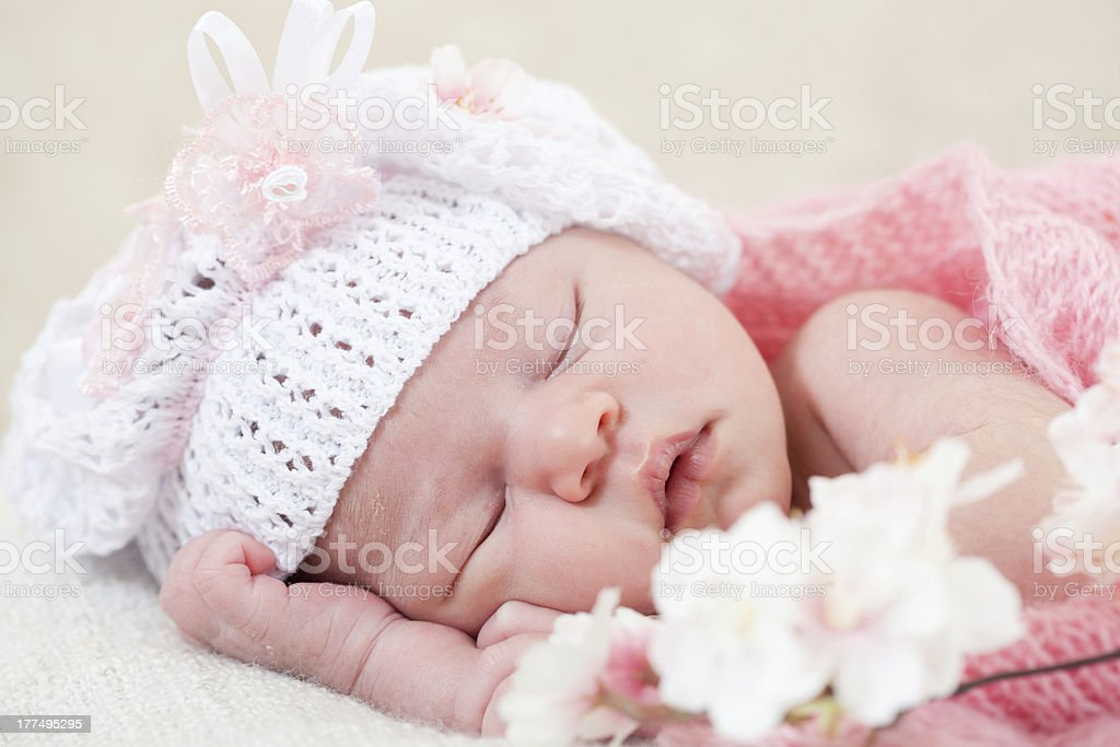 Sleeping baby in a knitted white hat, sleeping with flowers stock photo