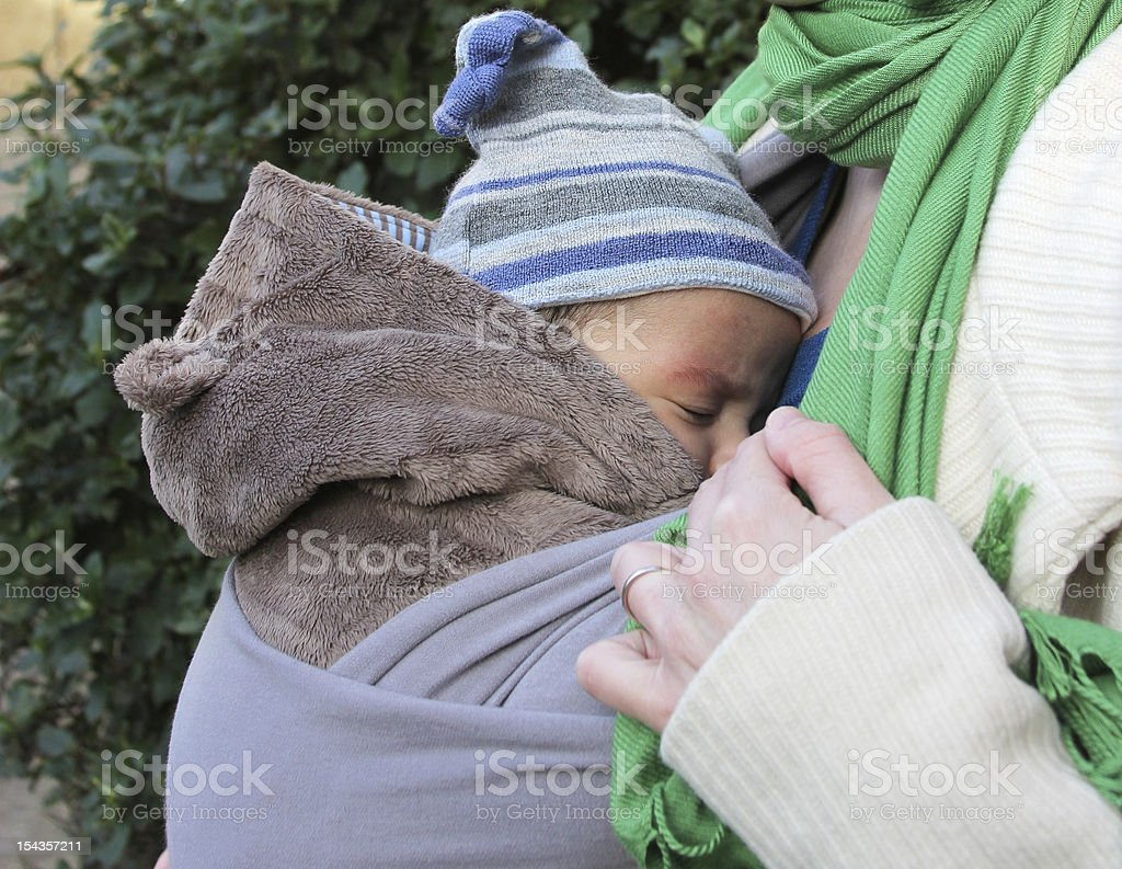 Sleeping baby in a slings - wedding ring on finger stock photo
