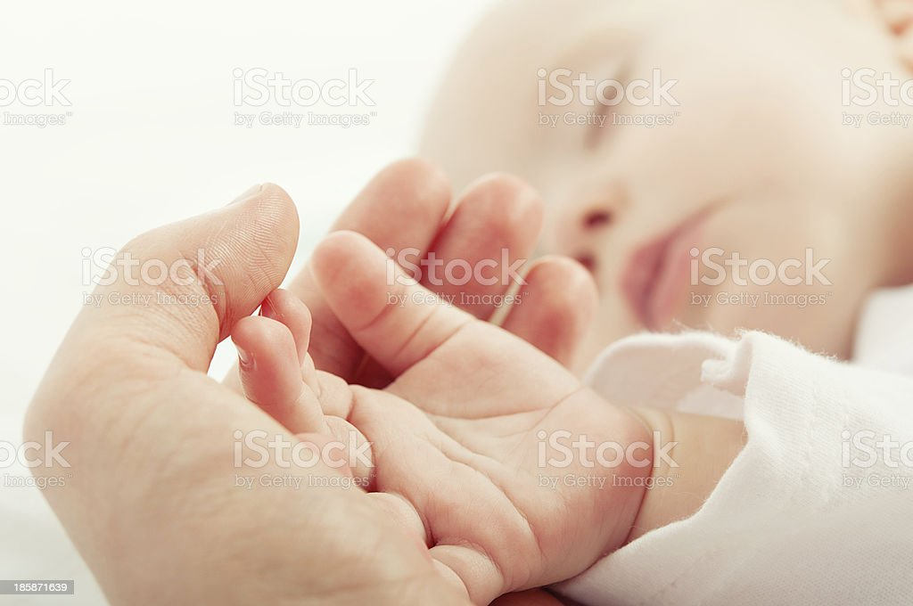 sleeping baby in hand of mother stock photo