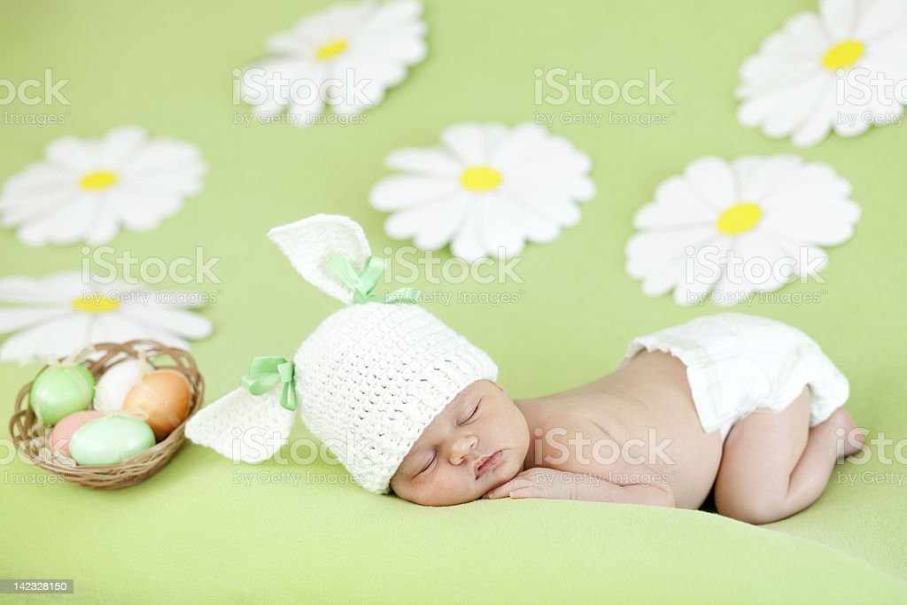 sleeping baby infant as rabbit and  Easter eggs in basket stock photo