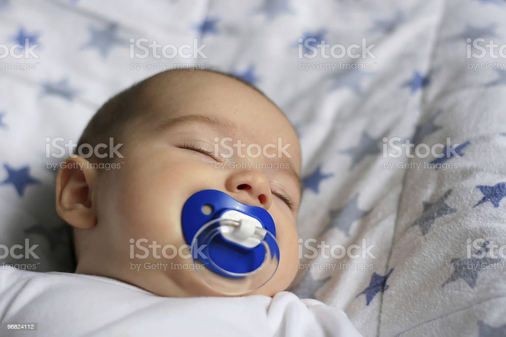 Sleeping baby with a blue pacifier stock photo