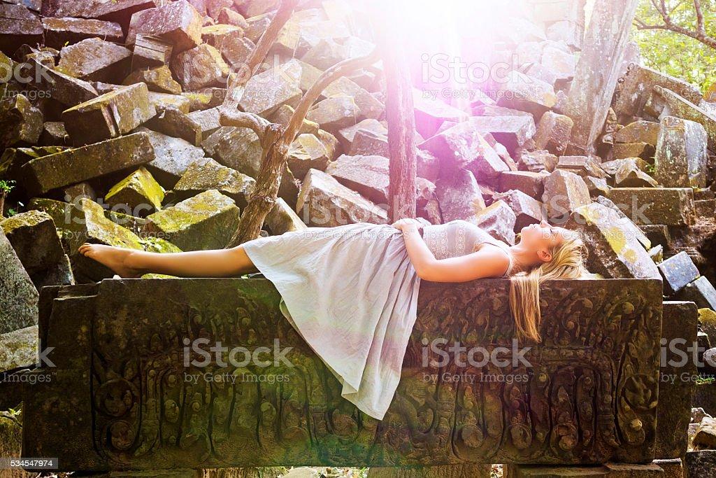Sleeping Beauty Fairytale Princess Laying on Rock Bed stock photo
