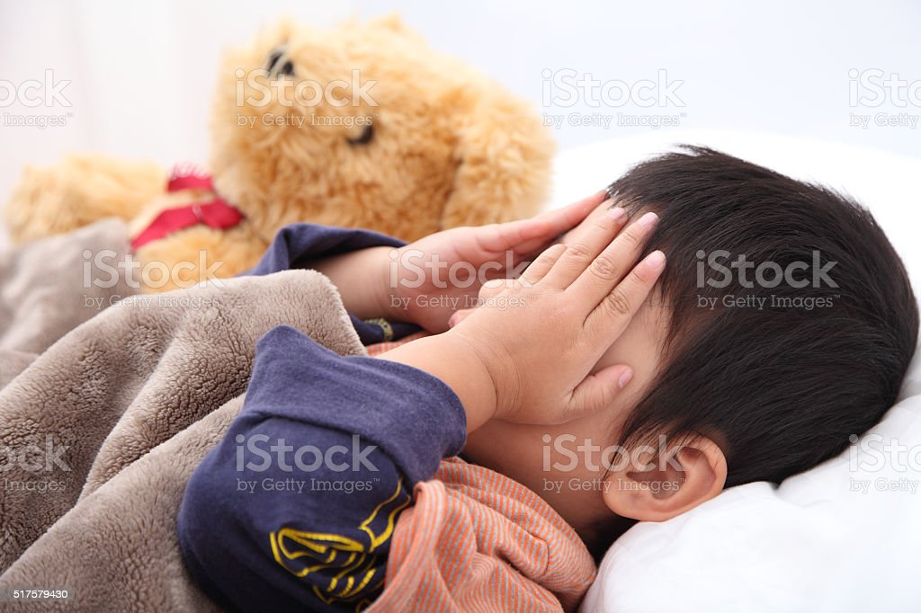 Sleeping child hands off covering face stock photo
