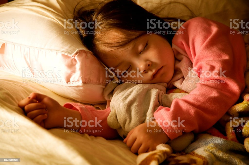 Sleeping child in pajamas on her bed royalty-free stock photo