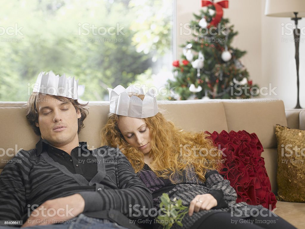 Sleeping couple wearing paper crowns at Christmas royalty-free stock photo