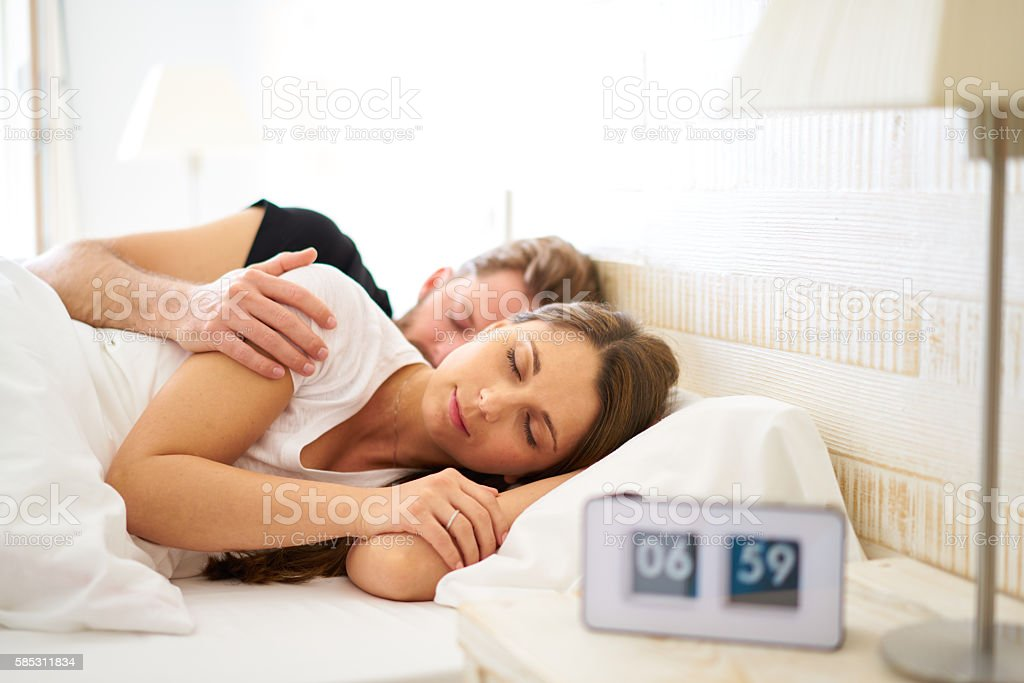 sleeping couple with blurred alarm clock before wakeup call stock photo