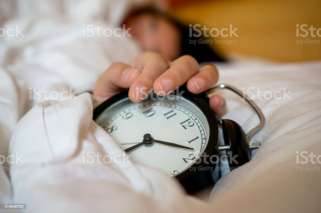 sleeping girl, alarm clock on bed stock photo