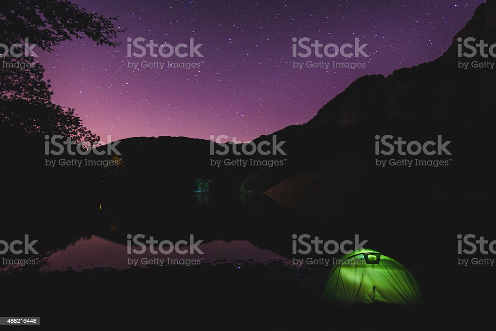 Sleeping In A Tent Near A Lake Under Starry Sky stock photo