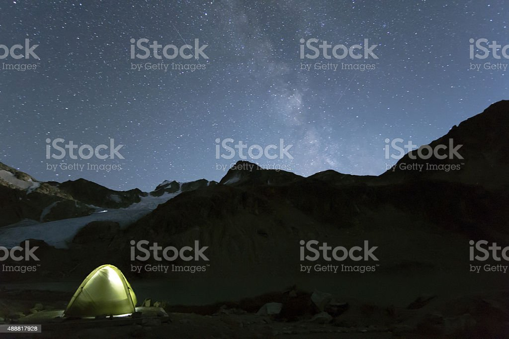 Sleeping in a tent under star dotted night sky stock photo