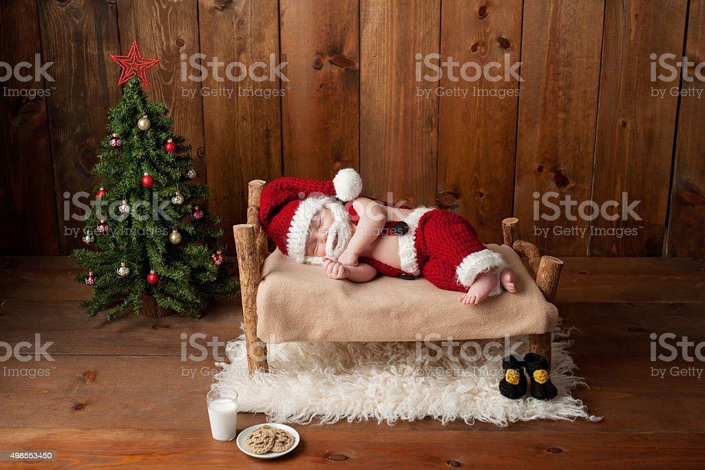 Sleeping Newborn Baby Boy Wearing a Santa Suit with Beard stock photo