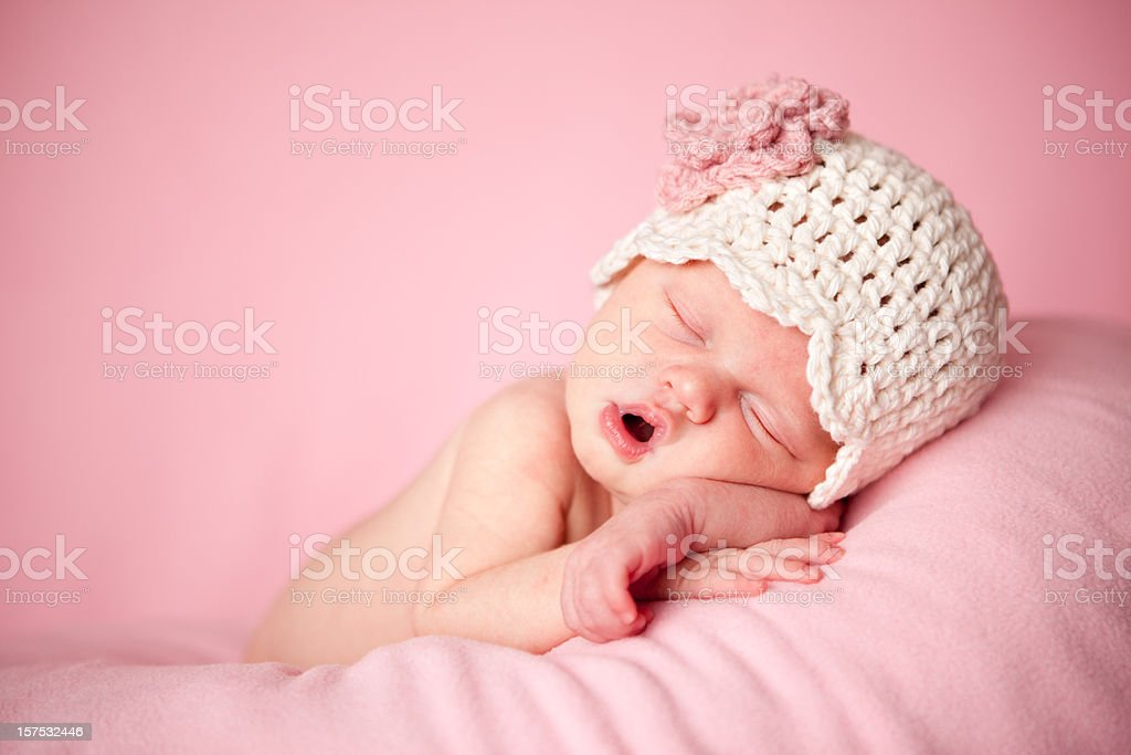 Sleeping Newborn Baby Girl Wearing a Crocheted Hat on Pink stock photo