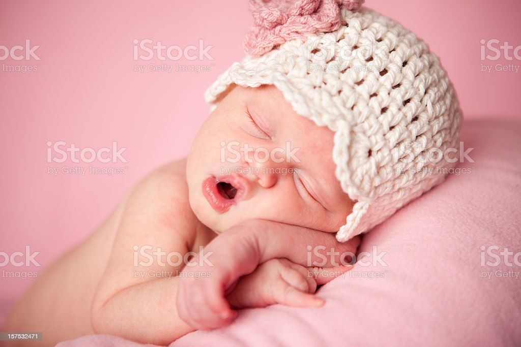 Sleeping Newborn Baby Girl Wearing a Crocheted Hat on Pink royalty-free stock photo