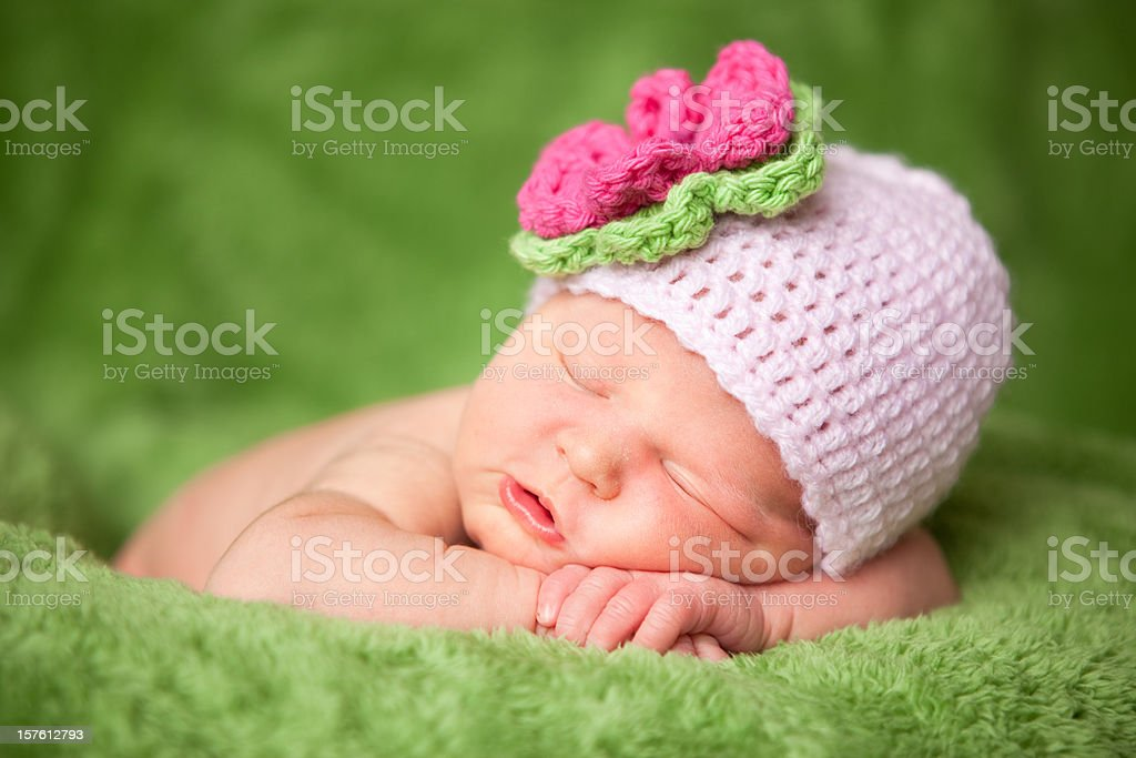 Sleeping Newborn Baby Girl Wearing Knit Hat with Flower stock photo