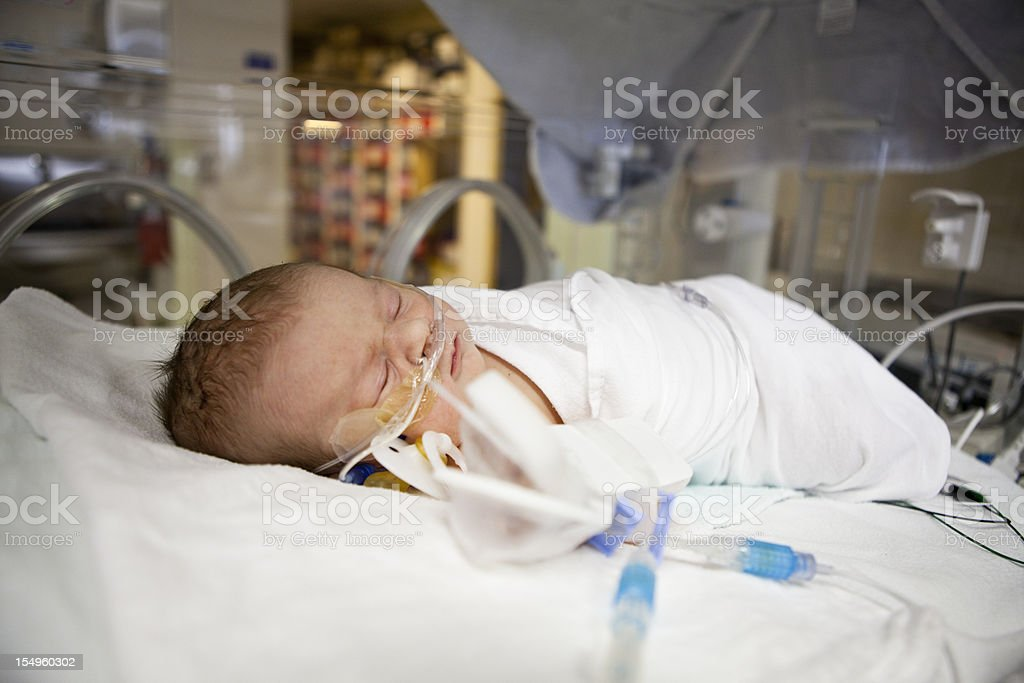 Sleeping newborn in hospital bed stock photo