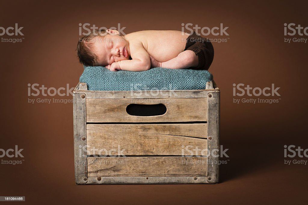 Sleeping Newborn Lying on an Old, Wood Crate royalty-free stock photo