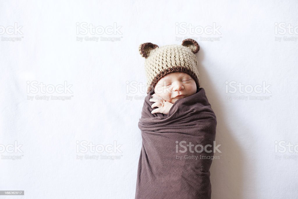 Sleeping Newborn Swaddled and Wearing a Bear Hat stock photo