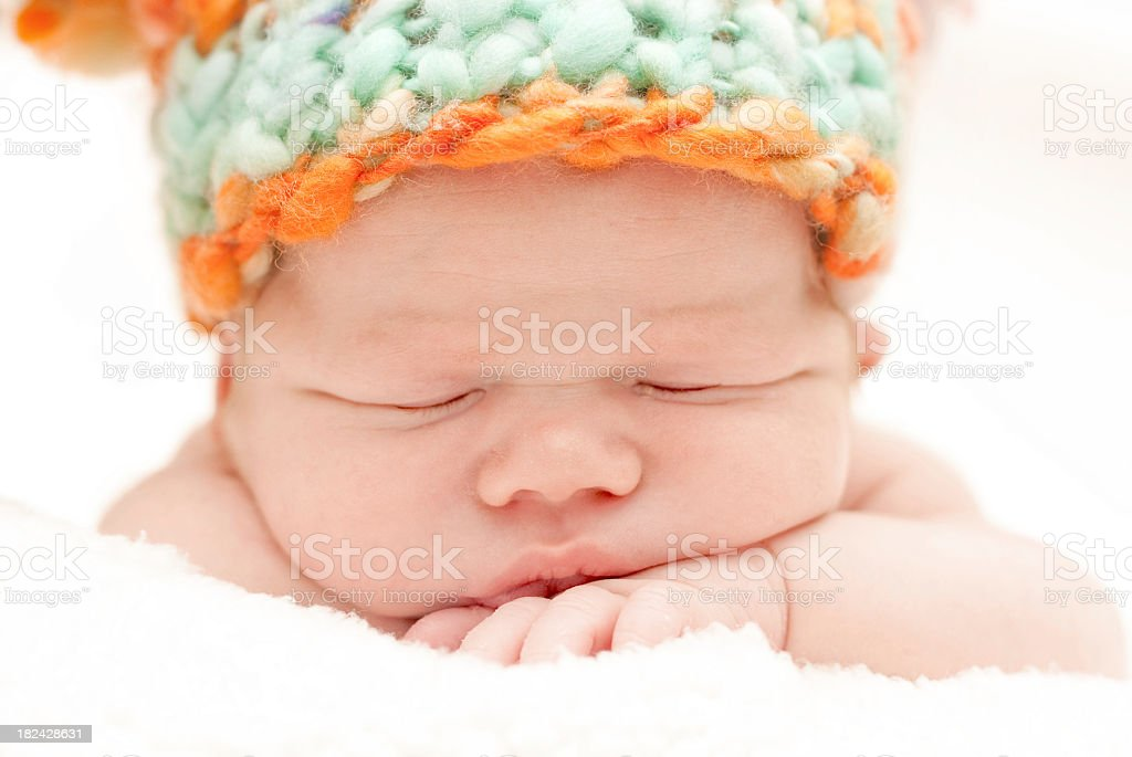 Sleeping newborn with colorful wool hat royalty-free stock photo