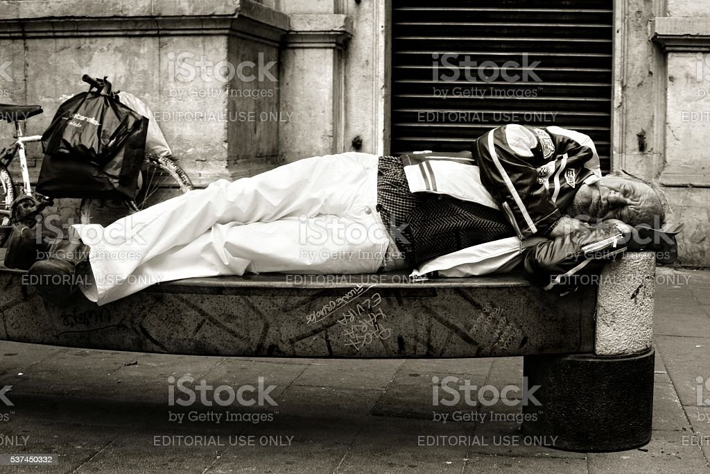 Sleeping on a bench Homeless old man Naples Italy stock photo