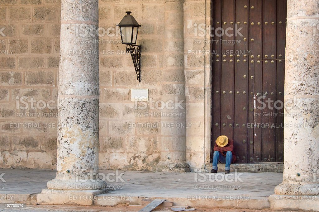 Sleeping on the door steps of a building in Cuba stock photo