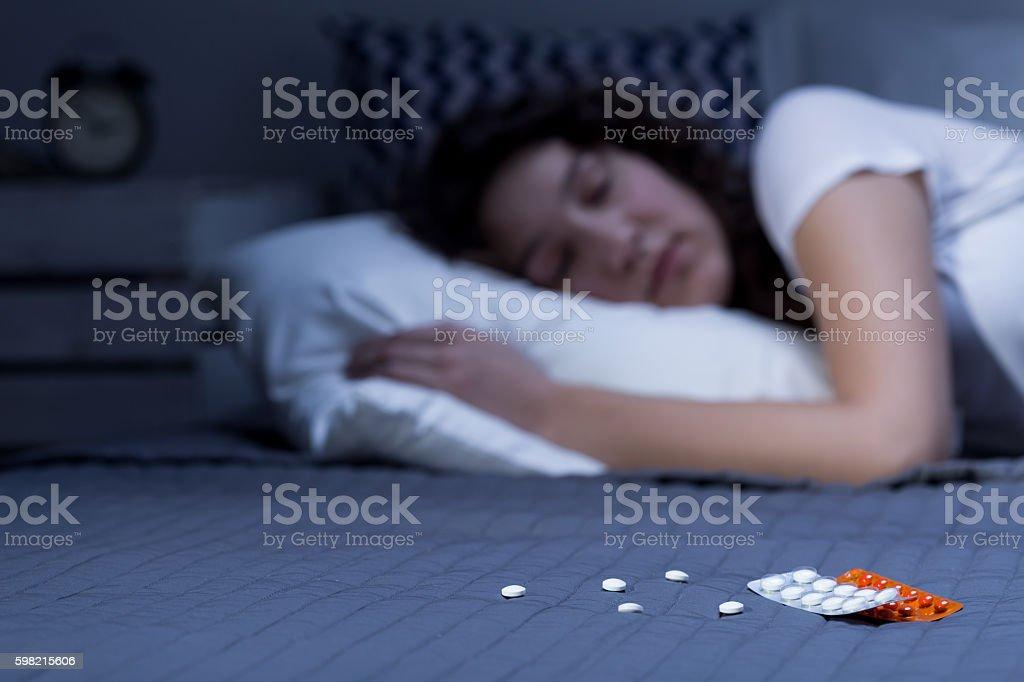 Sleeping pills on bed stock photo