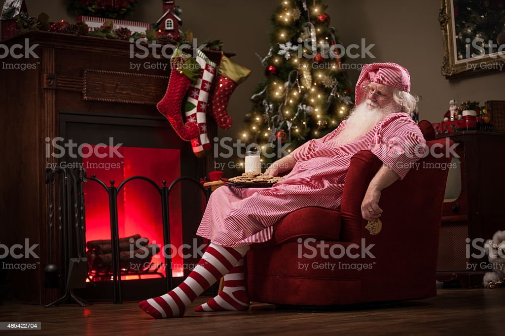 Sleeping Santa in Sofa Chair with Milk and Cookies stock photo