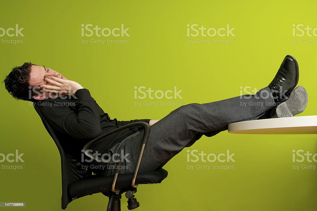 Sleeping with legs on table stock photo