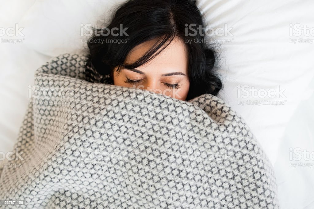 Sleeping woman cover face with blanket flat lay stock photo