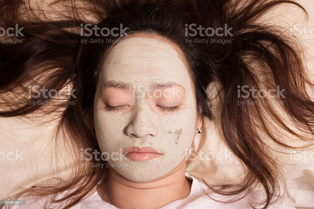 sleeping woman in clay mud facial mask on face stock photo