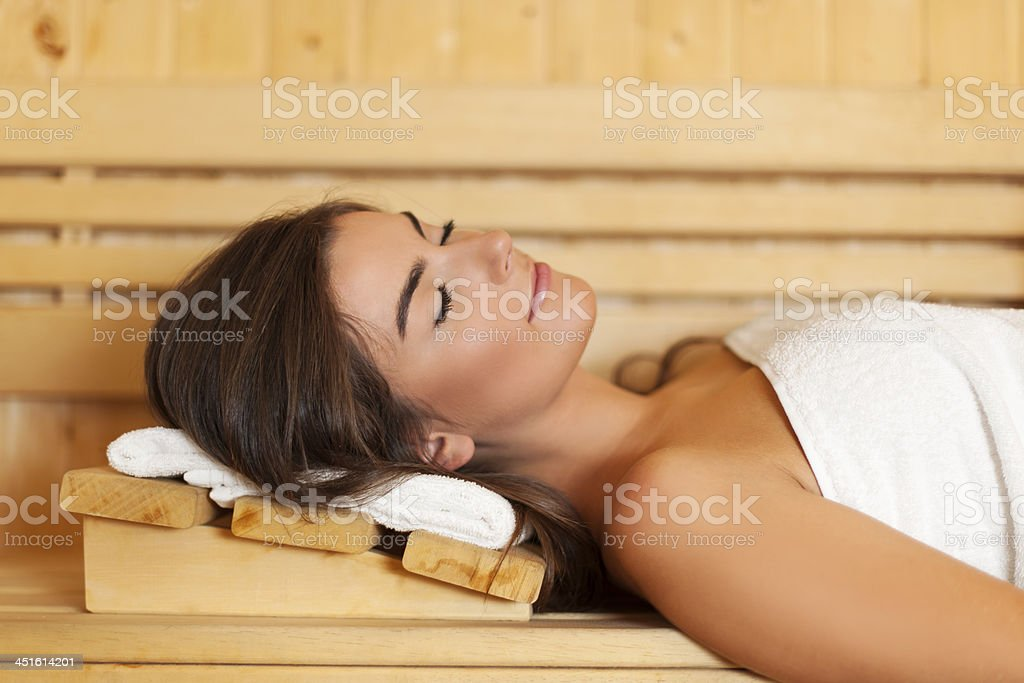 Sleeping woman laying in sauna stock photo